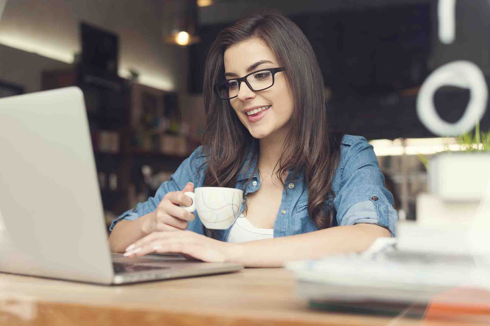 Women using laptop and drinking coffee