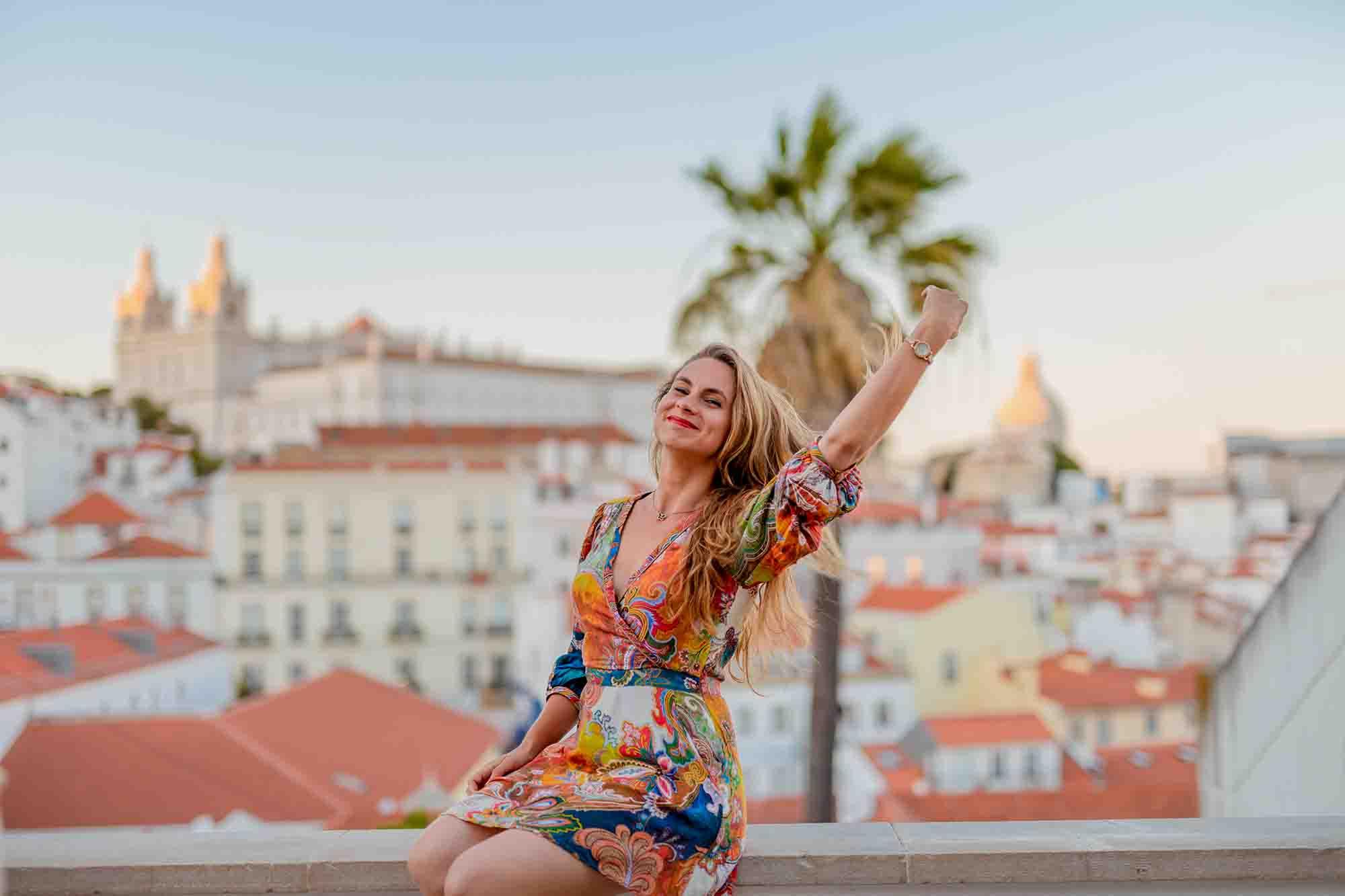 Elena Bicu sitting on a wall in Lisbon