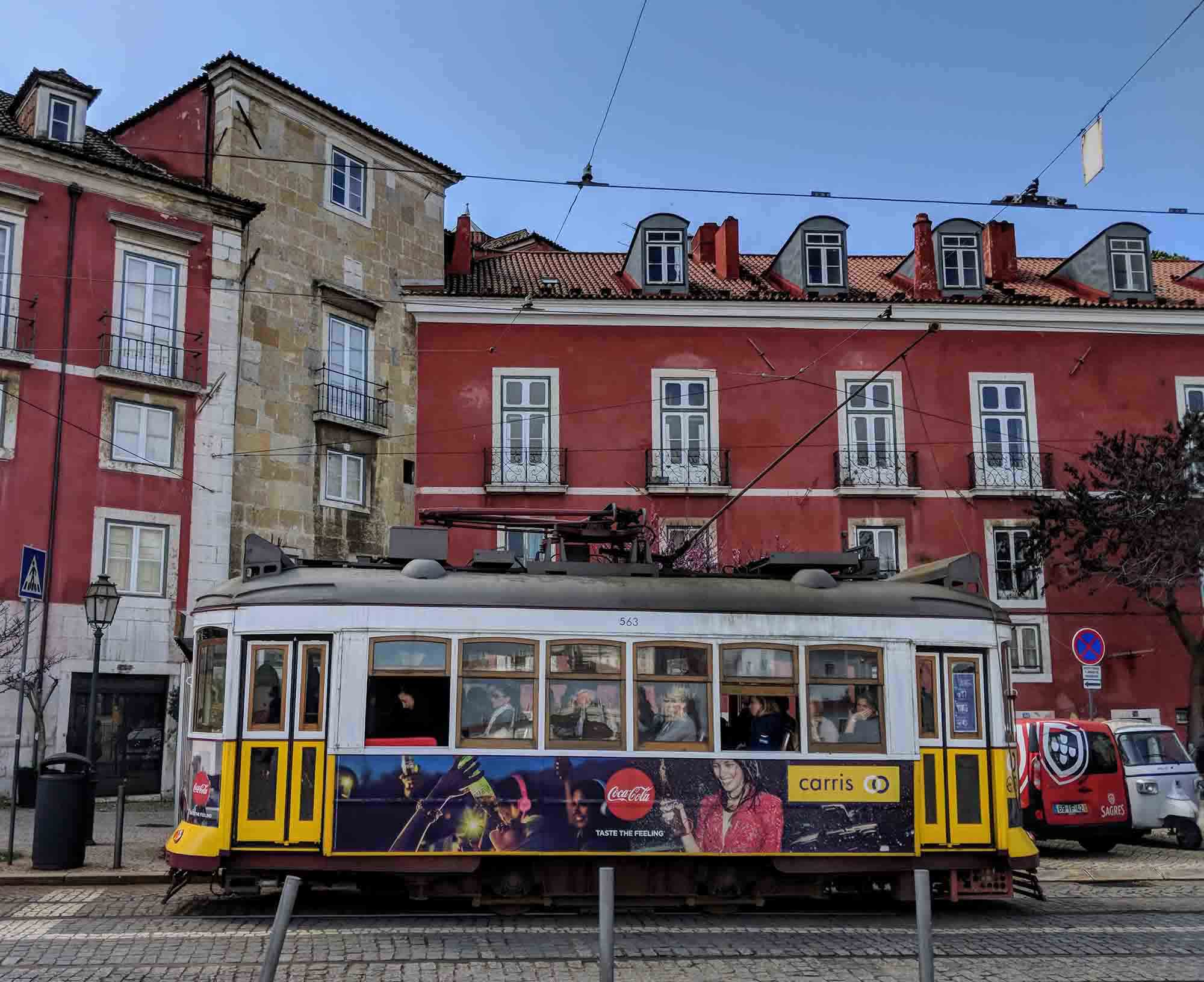 Lisbon tram in front of red building