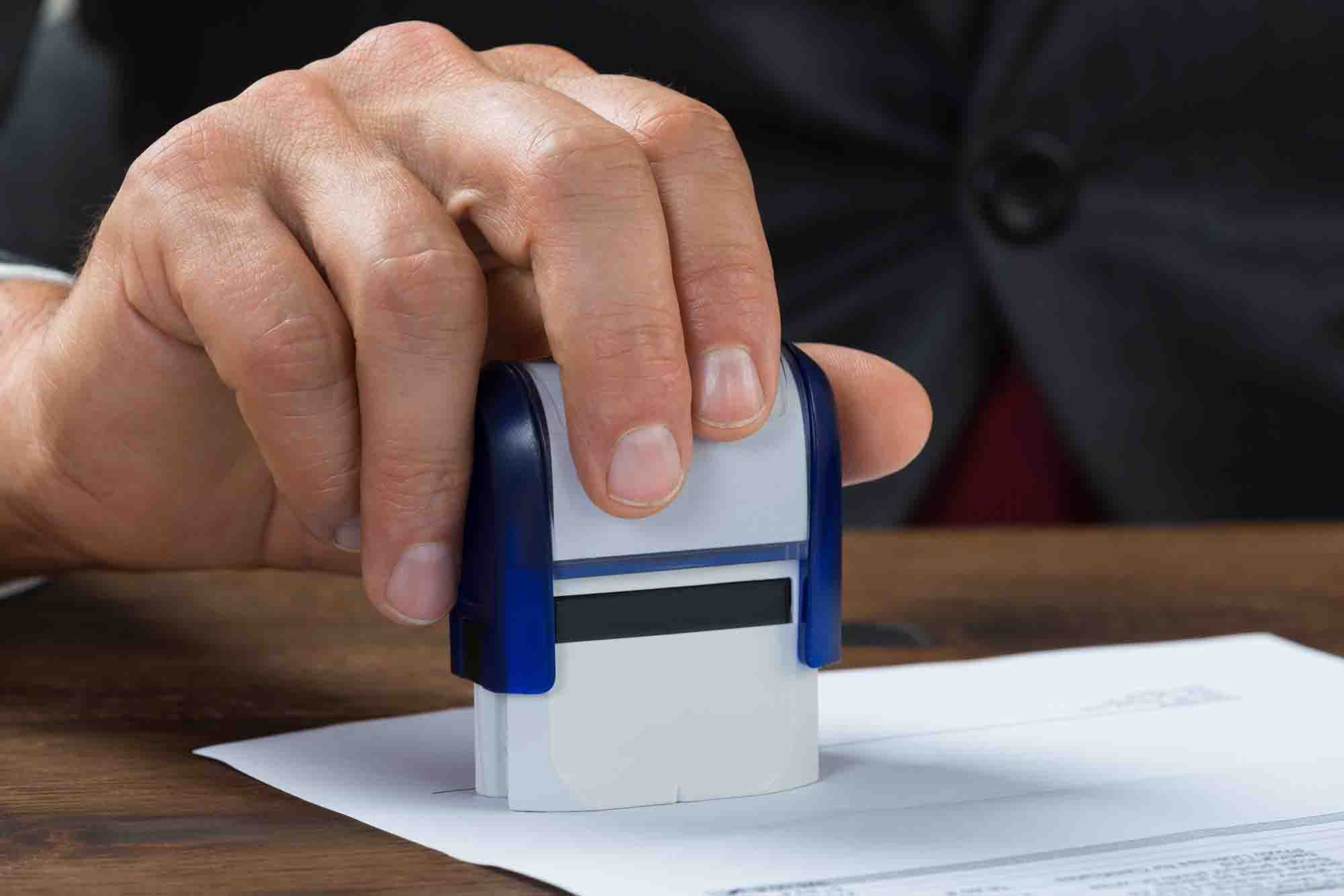 Businessman Stamping Document At Desk