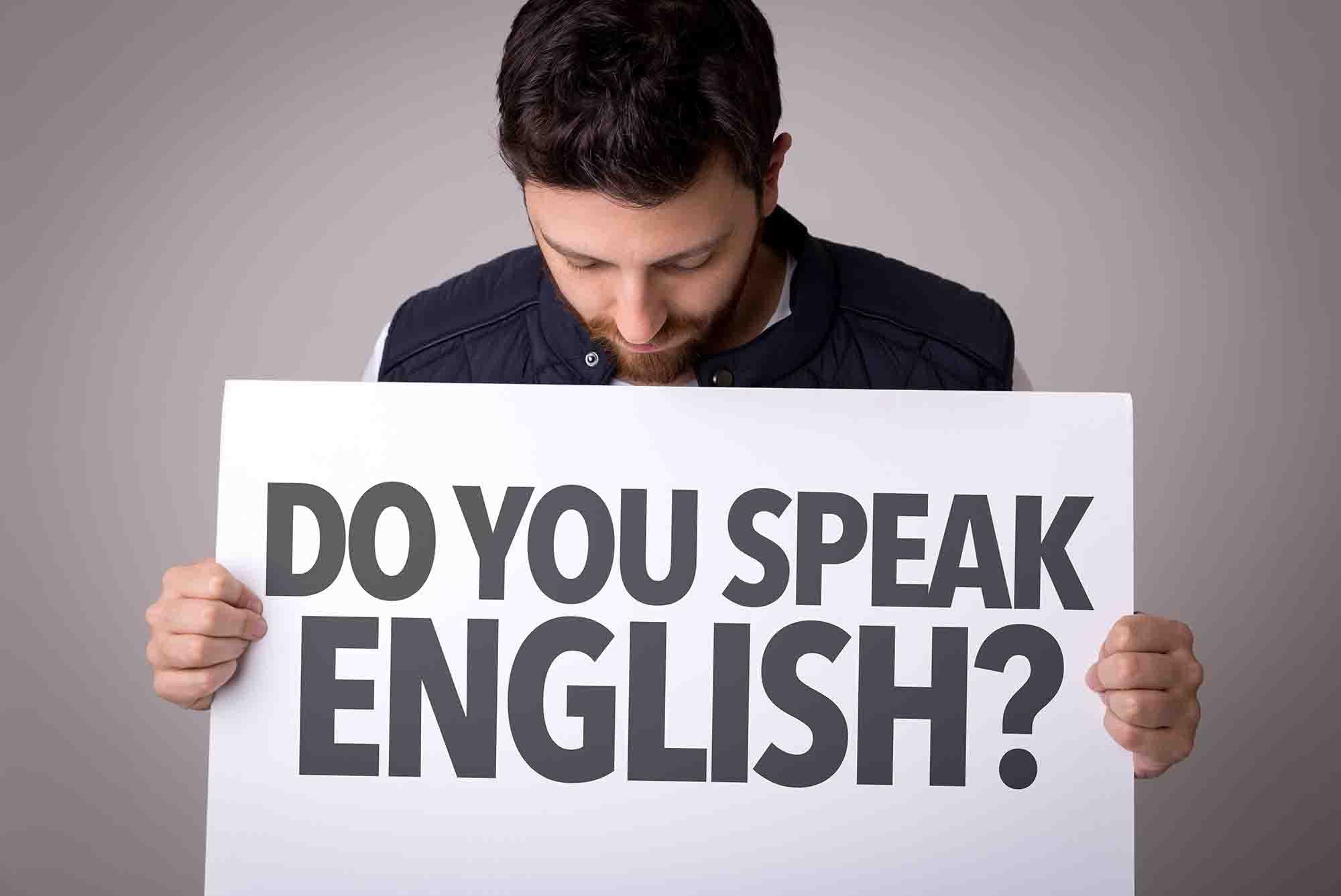 Man holding a sign saying, do you speak English?